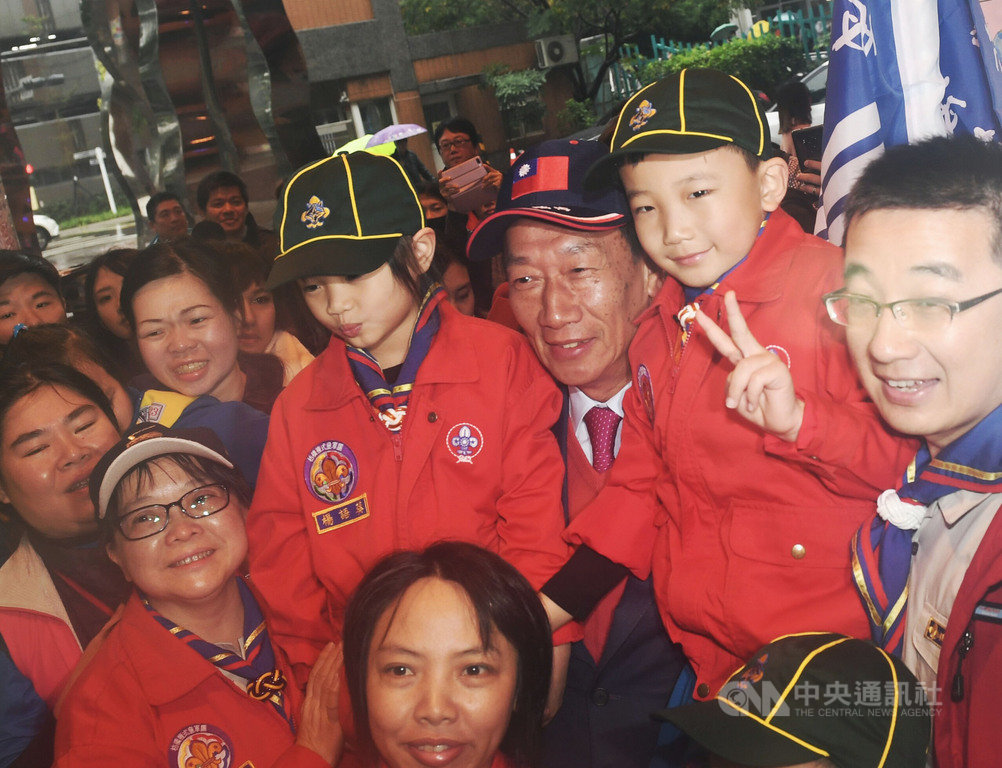鴻海董事長郭台銘(右3)9日上午出席新北市板橋國小創校120週年慶祝大會,抱起2名學生與家長們合影。中央社記者施宗暉攝 108年3月9日