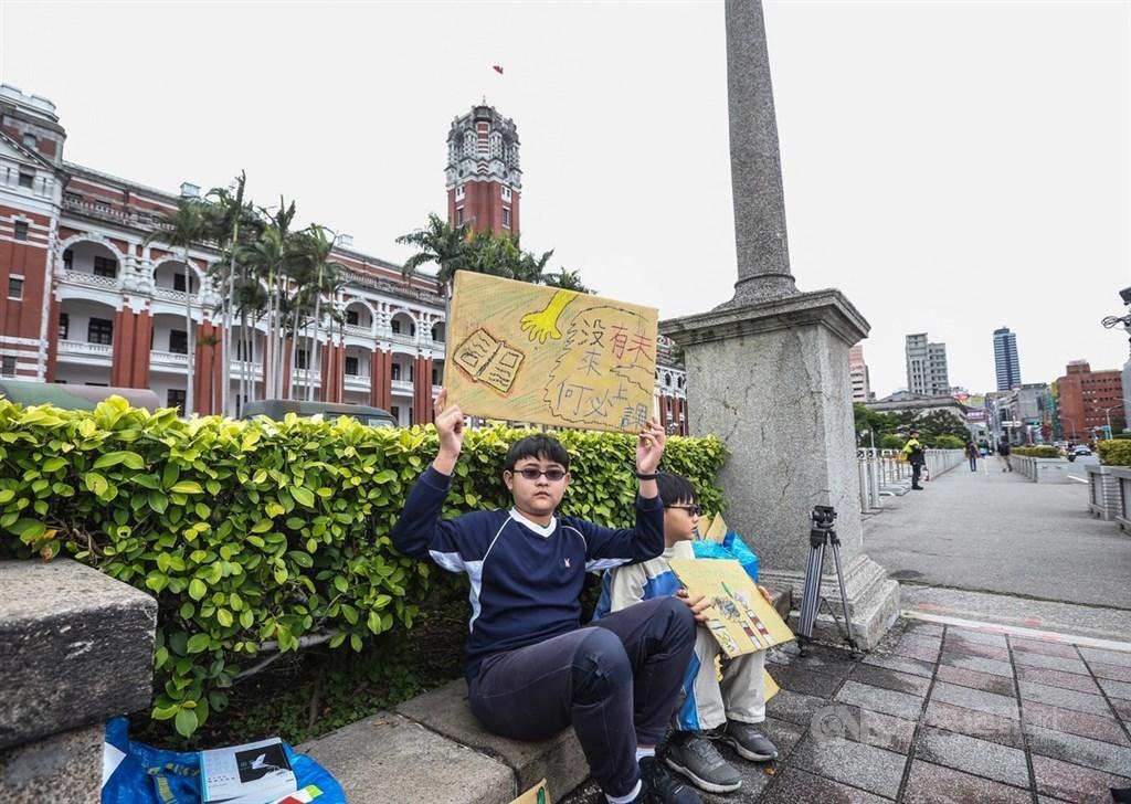 響應「Fridays for future Taiwan」315氣候行動,國小6年級學生楊子慶(左)15日在總統府前靜坐舉牌,希望政府採取行動對抗氣候變遷。中央社記者謝佳璋攝 108年3月15日