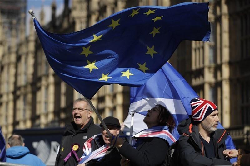 英國國會下議院14日通過延長里斯本條約第50條期限,3月29日的脫歐期限確定跳票。圖為反對英國脫歐的民眾在國會大廈外表達訴求。(美聯社提供)