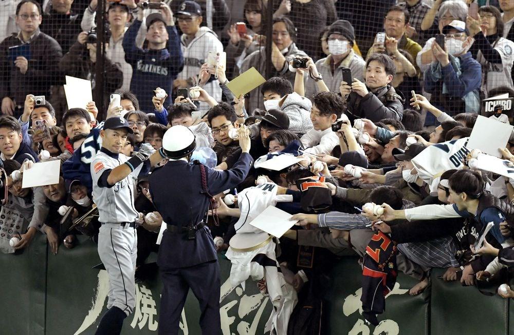 美國職棒水手隊17日與日職巨人隊進行熱身賽,水手隊日籍外野手鈴木一朗(前左)比賽前替球迷簽名。(共同社提供)