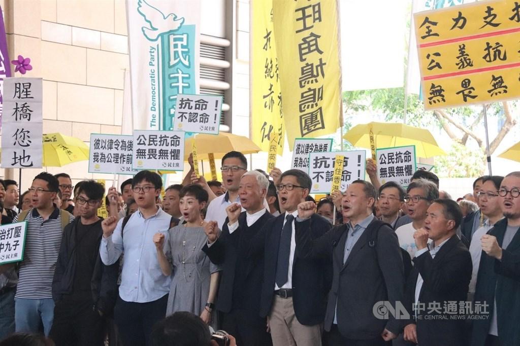 香港「占中」案9日上午法院裁決,「占中」發起人戴耀廷、陳健民和朱耀明被裁定「串謀公眾妨擾」罪名成立。圖為9名被告稍早進入法院前,與支持者齊呼口號要求真普選。中央社記者張偉強香港攝 108年4月9日