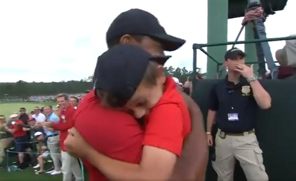 美國高爾夫名將老虎伍茲(前左)14日生涯第5度稱霸美國名人賽,賽後激動地擁抱兒子(前右),重現22年前與父親相擁的溫馨畫面。(圖取自twitter.com/TheMasters)