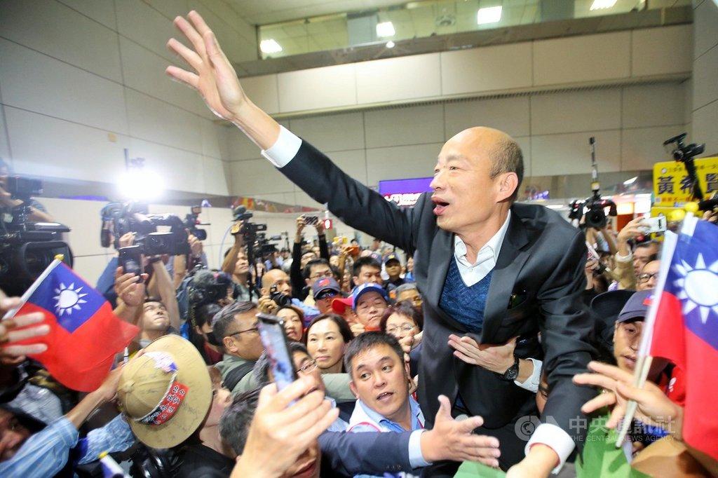高雄市長韓國瑜夫婦18日清晨搭機返抵國門,吸引許多支持民眾到機場接機,現場2名男子更抱著韓國瑜的大腿將他高高舉起,而韓國瑜也不斷揮手向支持群眾打招呼。中央社記者吳睿騏桃園機場攝 108年4月18日