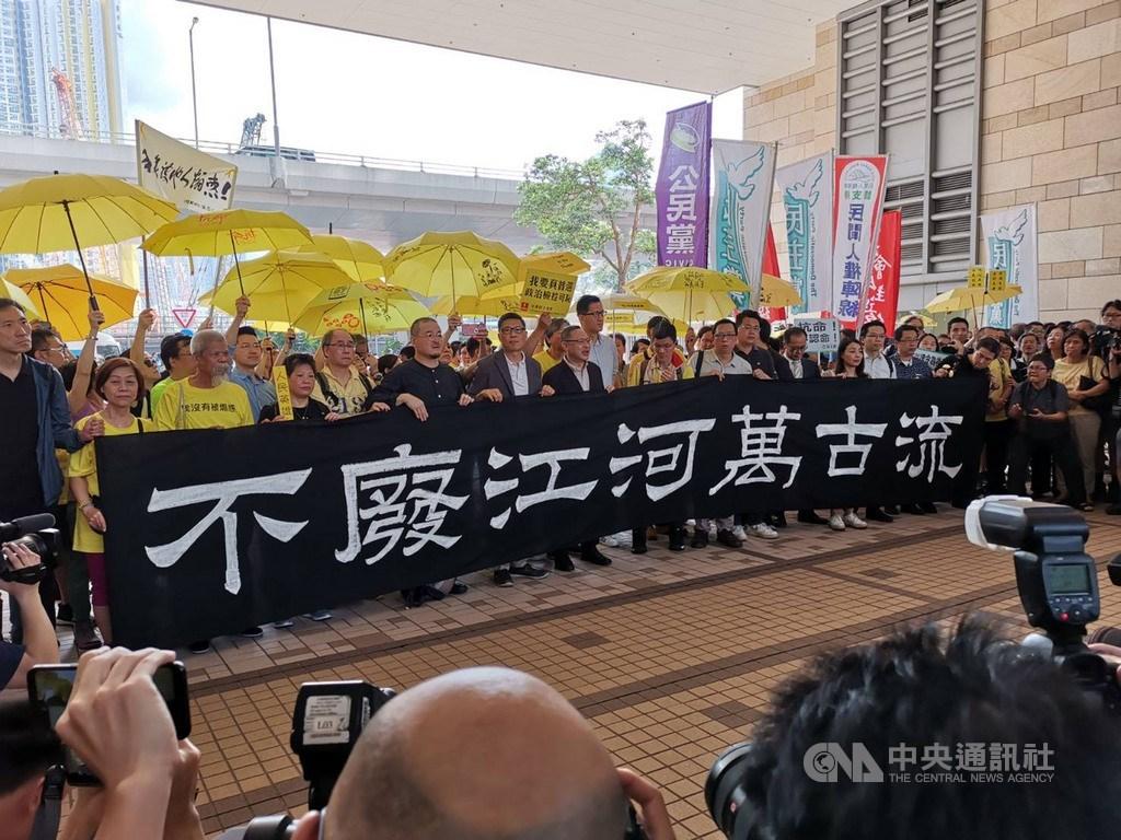 香港法院24日上午宣判占中案各名被告刑期前,9名被告包括「占中三子」在法庭前向媒體發表簡單談話,並與支持者撐黃傘,舉著「不廢江河萬古流」的標語。中央社記者張謙香港攝 108年4月24日