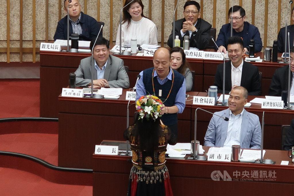 國民黨高雄市議員唐惠美(前)15日在市政總質詢時,送上一條琉璃珠項鍊給市長韓國瑜(2排左),還唱了一首「讀你」表達代表族人對他的相挺。中央社記者王淑芬攝  108年5月15日