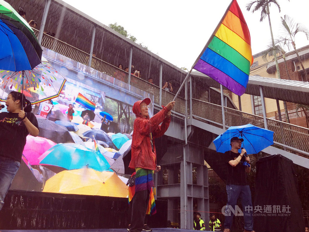 立法院會17日處理同婚專法草案,在二讀同性可辦結婚登記後,推動同志平權運動30多年的祁家威(中)也上台興奮揮舞彩虹旗。中央社記者吳欣紜攝  108年5月17日