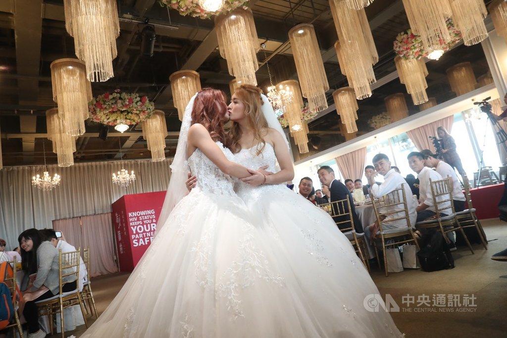 同婚專法過關,首場婚姻平權婚禮18日登場,同性伴侶穿上白紗,在眾人見證下親吻,接受大家的祝福。中央社記者吳家昇攝 108年5月18日