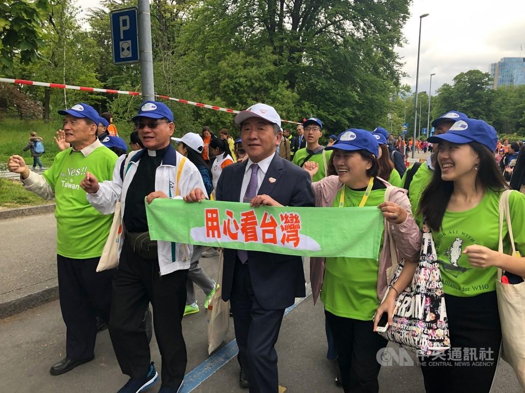 世界衛生組織(WHO)19日上午在聯合國歐洲總部前廣場舉辦Walk the Talk健走活動,世衛宣達團身穿TAIWAN CAN HELP的T恤上場。衛福部長陳時中(前排中)也手持「用心看台灣布條」參與。中央社記者戴雅真日內瓦攝 108年5月19日