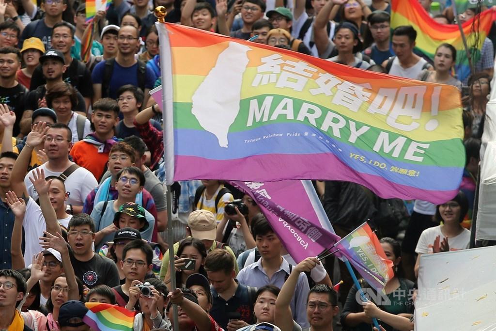 內政部戶政司22日在網站上公布「司法院釋字第748號解釋施行法施行後戶籍登記因應作為」,「同性結婚書約」載明為結婚人。圖為立法院17日三讀通過同婚專法,大批挺同民眾在院外揮舞彩虹旗。(中央社檔案照片)