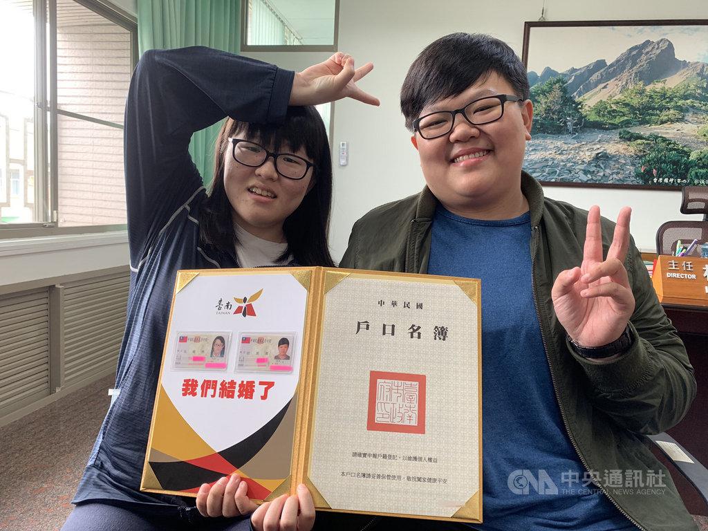 同婚登記24日上路,同性伴侶吳暐樂(左)、岩湘蓁(右)成了台南第一對完成登記的佳偶,看到身分證配偶欄有著對方的名字,兩人高興地比起「YA」的勝利手勢。中央社記者張榮祥台南攝  108年5月24日
