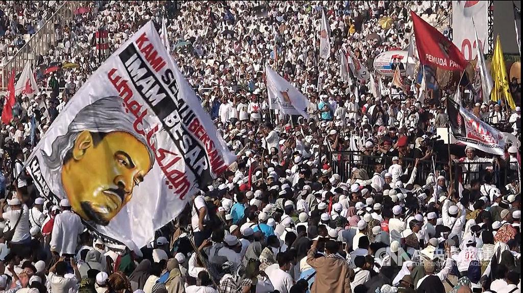 印尼網友最近連署要求解散伊斯蘭防衛者陣線、並撤銷其精神領袖哈比比利奇的印尼公民身份。圖為支持普拉伯沃的群眾在選前的造勢場合揮舞哈比比利奇的大旗。(檔案照片)中央社 108年6月9日