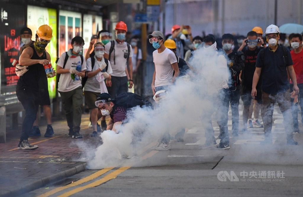 香港12日因為逃犯條例修訂草案二讀,大量民眾聚集抗議,警方下午4時後陸續向民眾發射催淚彈意圖驅離,部分穿戴護具的抗議民眾想撿起催淚彈。中央社記者王飛華攝 108年6月12日