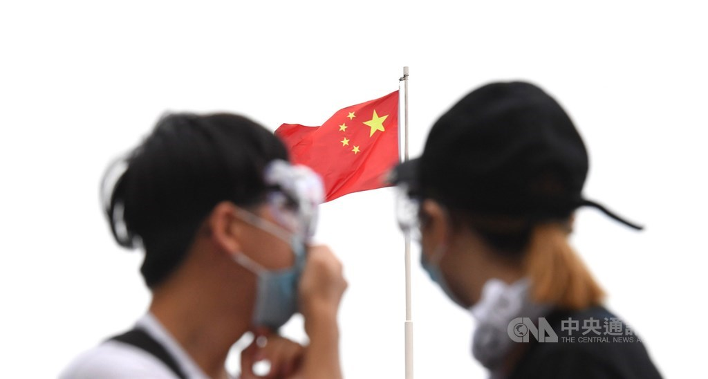 香港反送中示威爆發警民衝突,特首林鄭月娥定調為暴動,堅持修訂逃犯條例。圖為12日戴護目鏡、口罩抗爭的香港民眾望向一旁的五星旗。(中央社檔案照片)