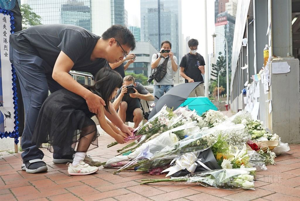 香港一名支持反對修訂逃犯條例的男子15日晚間在金鐘太古廣場高處懸掛示威橫額時,墜樓送醫不治死亡,16日上午一名家長帶著孩子到場獻花,盼亡者安息。中央社記者裴禛香港攝 108年6月16日