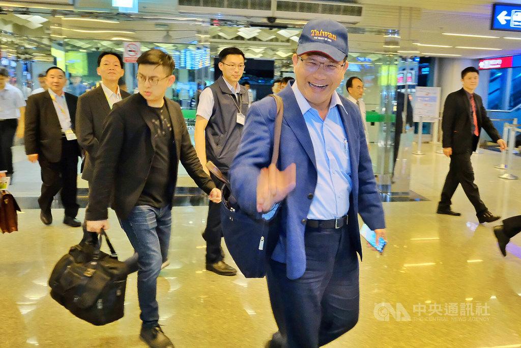 交通部長林佳龍(前右)18日晚間率團搭機出訪,將代表中華民國前往貝里斯慶祝兩國建交30週年,穿著深藍色西裝的他戴著一頂棒球帽、背著公事包相當低調。中央社記者吳睿騏桃園機場攝 108年6月18日