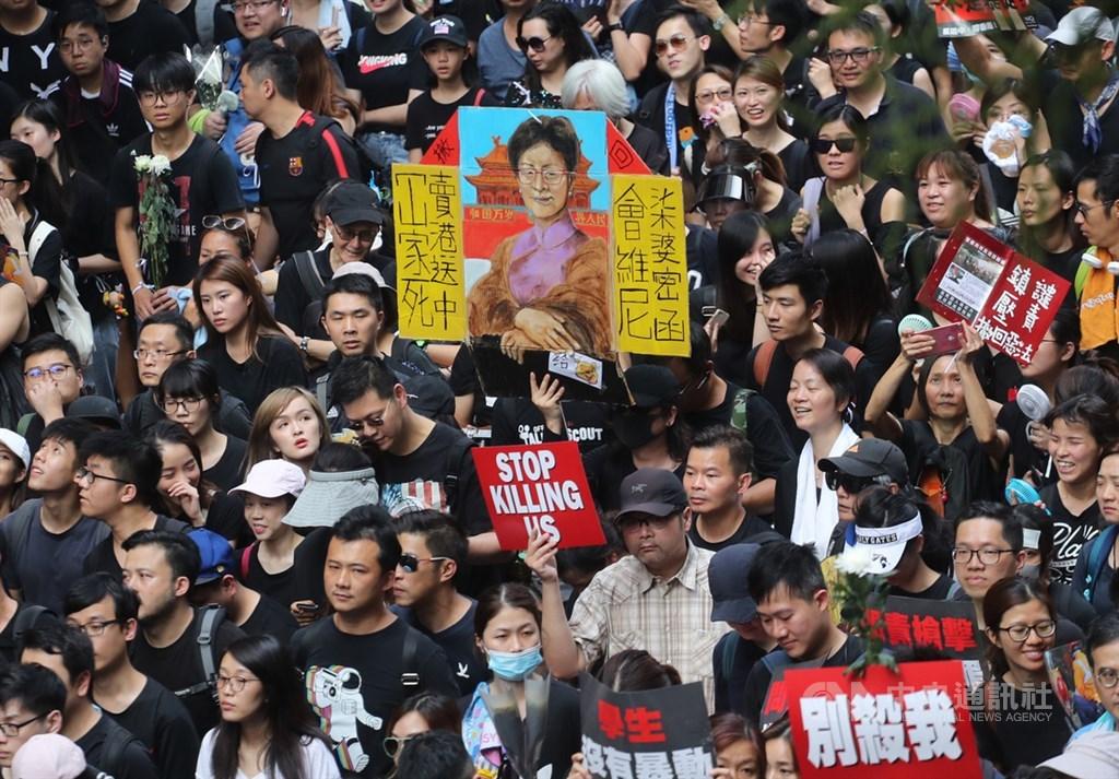 香港泛民主派團體民間人權陣線16日再次發起反修訂逃犯條例大遊行,大批民眾身穿黑衣走上街頭,有人高舉繪製的標語要求行政長官林鄭月娥下台。(中央社檔案照片)