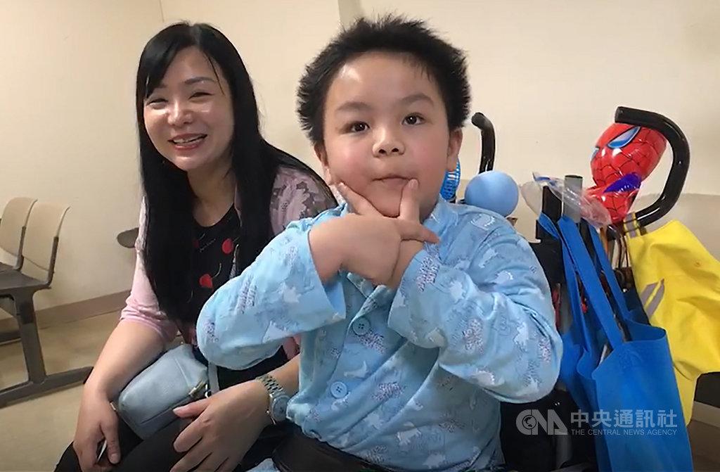 台鐵普悠瑪列車去年在宜蘭翻覆,身受重傷的7歲男童謝沛帛(右)一度昏迷,4個月後甦醒。謝沛帛母親徐美珍(左)19日帶他到醫院回診時,謝沛帛身體已好轉,還會用手勢向人打招呼,他也將在9月重返校園生活。中央社記者沈如峰宜蘭攝 108年6月19日