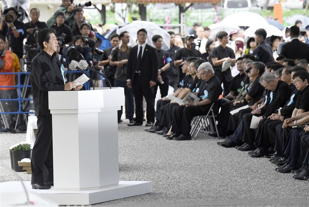 日本沖繩縣23日追悼沖繩戰役陣亡者,首相安倍晉三(前左)出席致詞,遭台下民眾嗆「滾回去」。(共同社提供)
