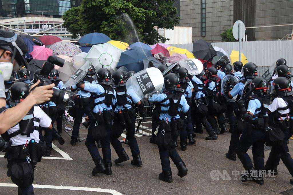 香港主權移交22週年,七一大遊行1日預計登場。香港警方早上7時30分與占據馬路、阻止升旗典禮的示威人士衝突。圖為警察用胡椒噴劑對付示威者。中央社記者張謙香港攝 108年7月1日