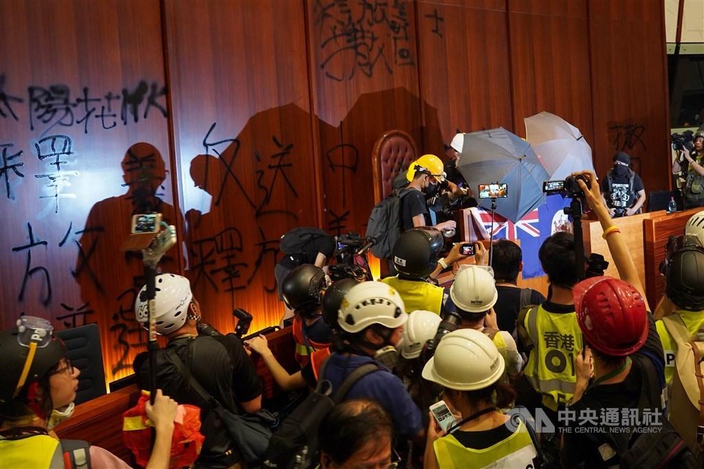 反對逃犯條例修訂的香港民眾1日持續抗爭,示威者晚間衝進立法會後占領議場,並在牆上噴漆表達訴求。中央社記者裴禛香港攝 108年7月1日