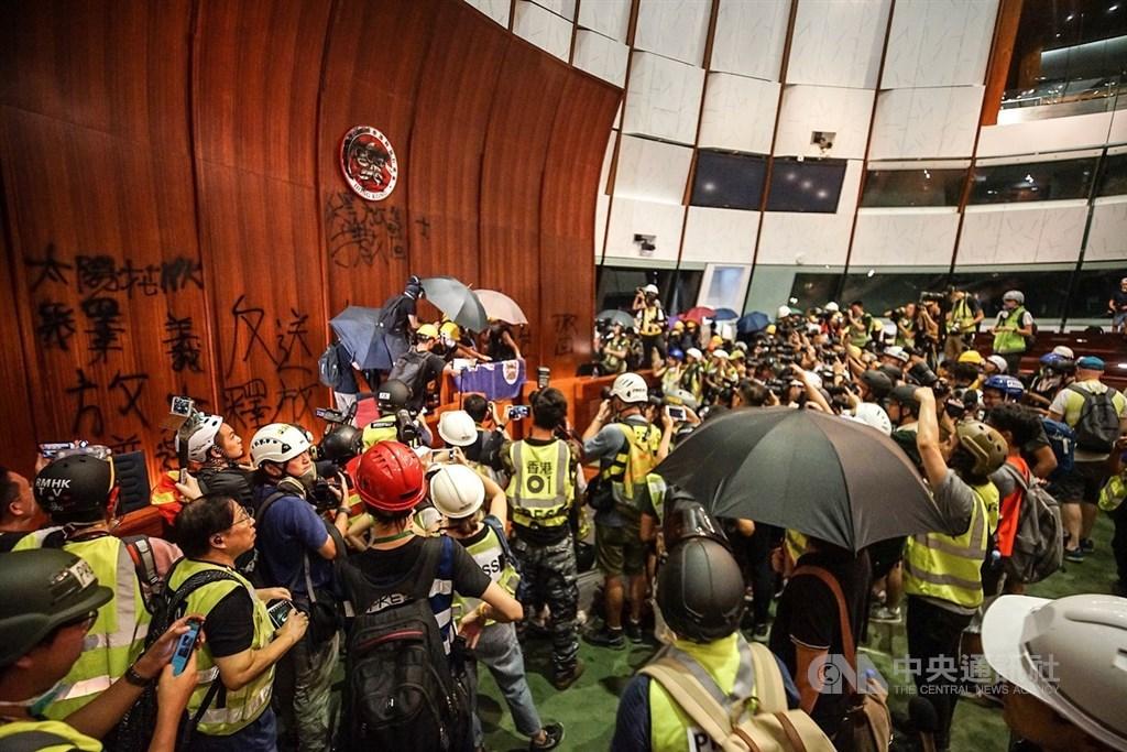 數以百計的香港示威者1日晚間撬開鐵門後闖入立法會,進一步占領議場,不但噴漆將特區政府的區徽塗黑,並噴上「太陽花HK」、「林鄭下台」、「釋放義士」等口號。中央社記者裴禛香港攝 108年7月1日