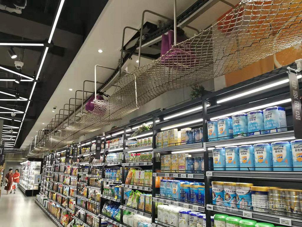 當消費者步行在貨架間選購商品時,頭頂上方的輸送帶也忙著運送網購物品,這成為中國超市盒馬鮮生展示說明線上線下邊界消融的場景。(資料照片)中央社記者陳家倫寧海傳真 108年7月14日
