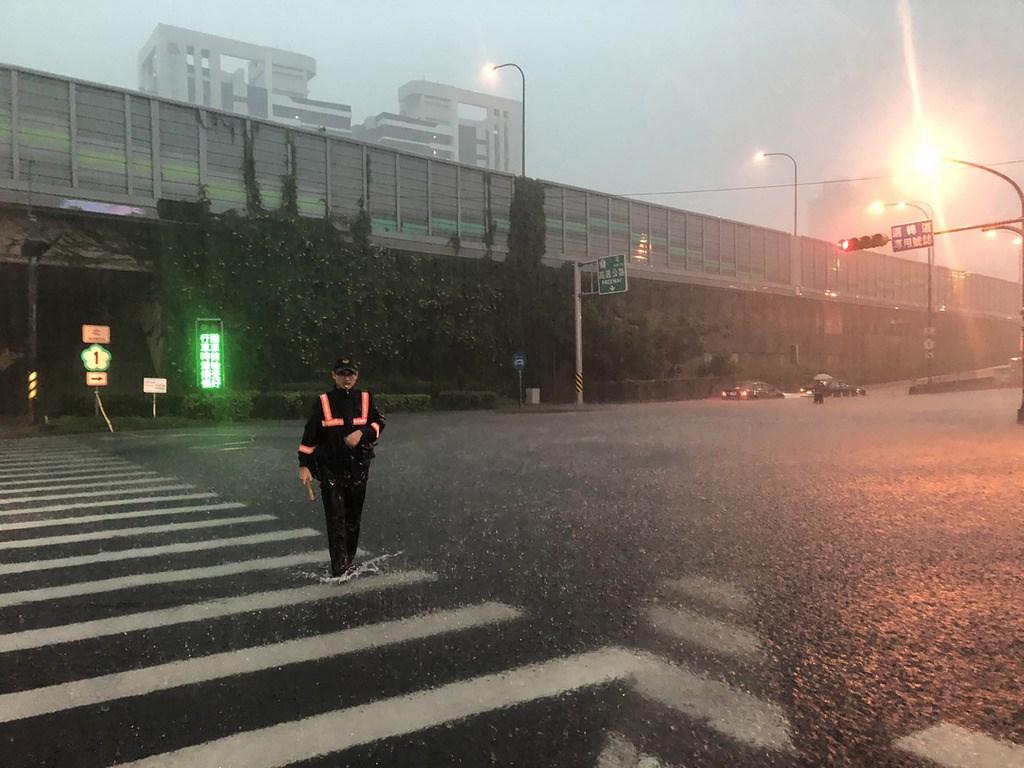 高雄市19日下午下起傾盆大雨,造成市區多處發生積淹水情形,人車受困事件頻傳,警方冒雨上街協助疏導、管制,以維護民眾安全。(民眾提供)中央社 108年7月19日