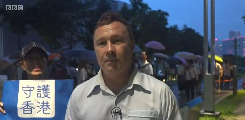 香港建制派20日發起集會,英國BBC記者麥迪文(前右)前往香港現場連線報導,卻遭經過的挺中民眾嗆聲。(圖取自BBC網頁bbc.com)