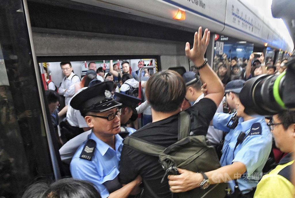 10多名著黑衣的反送中示威者24日早上響應號召,在港島地鐵金鐘站阻礙列車行走,造成港島線地鐵一度被癱瘓延誤10至15分鐘。(中通社提供)中央社 108年7月24日