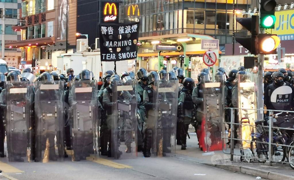 香港「反送中」未歇,27日「光復元朗」遊行再度聚集大批群眾,晚間7時,防暴警察高舉黑旗,警告示威者將施放催淚彈。 中央社記者張謙攝 108年7月27日