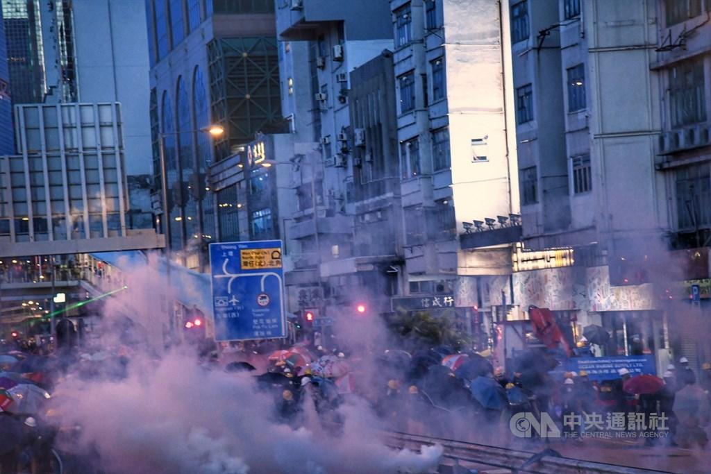 香港中環遮打花園28日舉行的追究警方濫權集會,演變為大規模「自主」遊行,香港警方晚間開始大規模使用催淚彈驅離,部分示威者以雨傘防護。中央社記者王飛華香港攝 108年7月28日