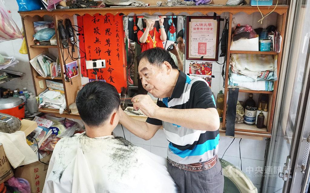 華山基金會30日在台北舉行「華山人瑞理髮好手藝 歡度過父親節」記者會,從事理髮超過70年的人瑞理髮師林能火(右)現場展示理髮手藝。中央社實習記者房荷庭攝  108年7月30日