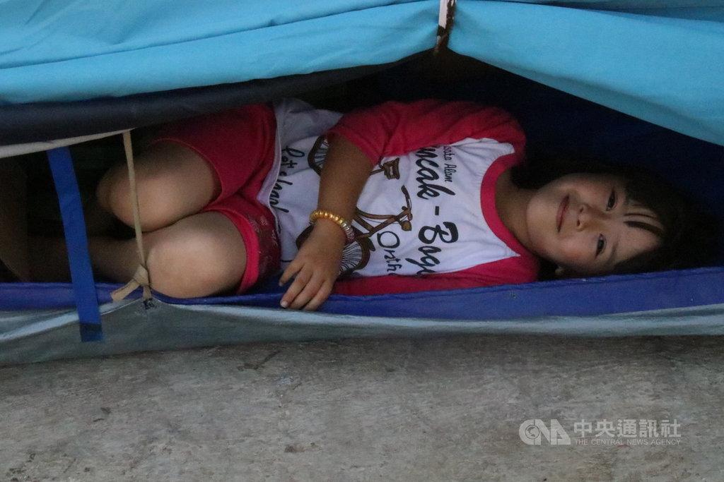 住在雅加達西區卡里德勒斯廢棄軍營難民營的阿富汗小女孩看到中央社記者前來採訪,好奇地從帳篷探頭出來看看,大方對攝影機微笑。中央社記者石秀娟雅加達攝。 108年8月3日