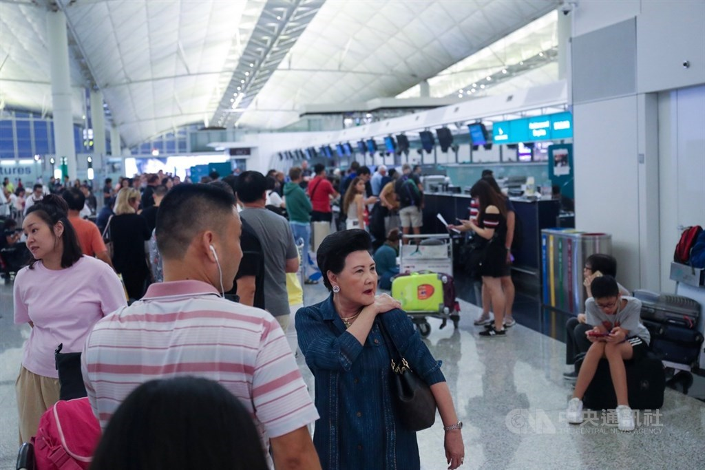 香港反送中示威者號召全民罷工、百萬人塞爆機場,造成香港機場12日下午4時起全數航班取消,13日班機航班大亂,旅客在櫃台前排隊等候。中央社記者吳家昇攝 108年8月13日