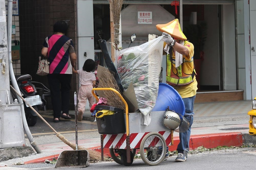 有民眾向媒體投訴,指台北市環保局禁止清潔人員穿制服進入便利商店,副局長盧世昌16日說,並非禁止,而是曾多次接獲民眾投訴指清潔隊員在便利商店打牌、喧嘩,才發公文。圖為清潔隊員清掃街頭。(示意圖/中央社檔案照片)