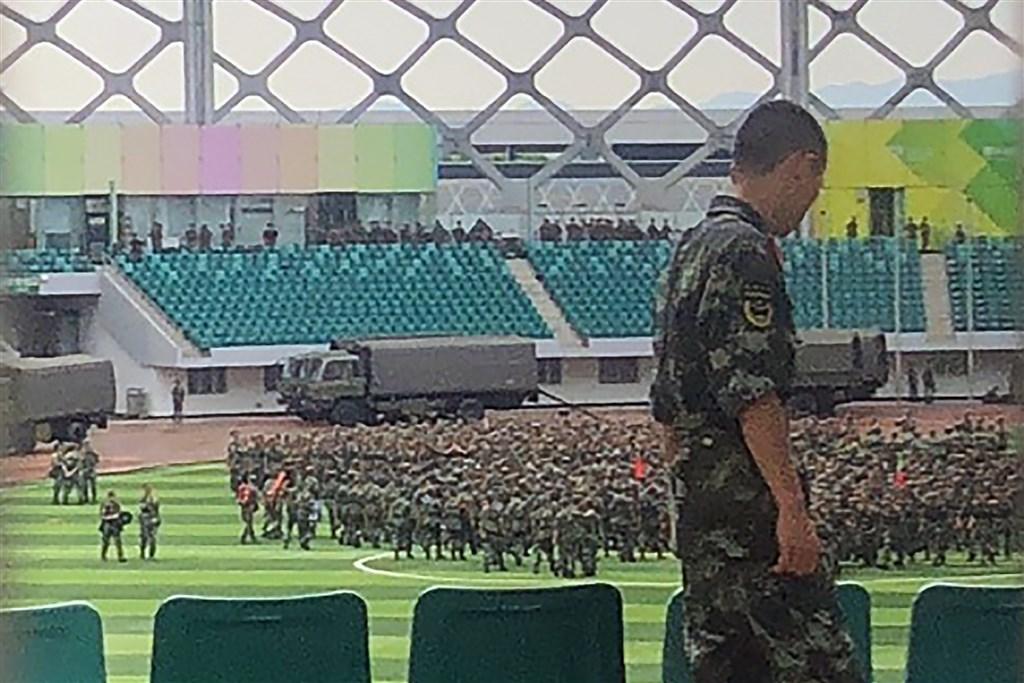 一名法新社記者15日目擊,數千名中國軍事人員在與香港毗鄰的深圳市一座體育館揮舞紅色旗幟進行操練。(法新社提供)