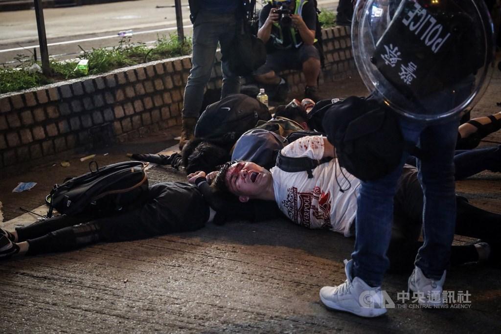 美國總統川普15日說,他不希望看到中國殘暴鎮壓香港的示威者。圖為11日反送中示威者被港警壓制在地。(中央社檔案照片)