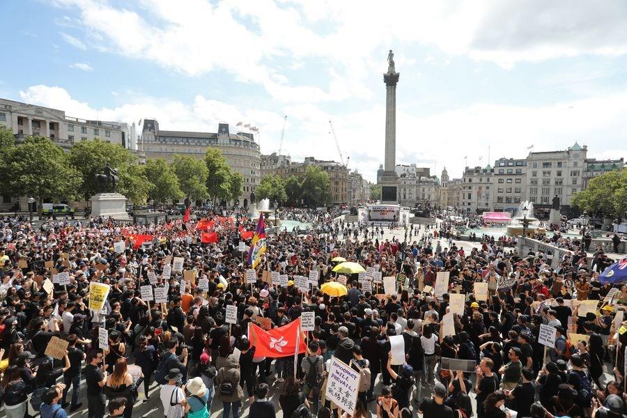 上千名海外港人17日在倫敦遊行,高呼「香港加油」;但支持中國群眾高舉五星旗挑釁,對港人叫囂。(法新社提供)