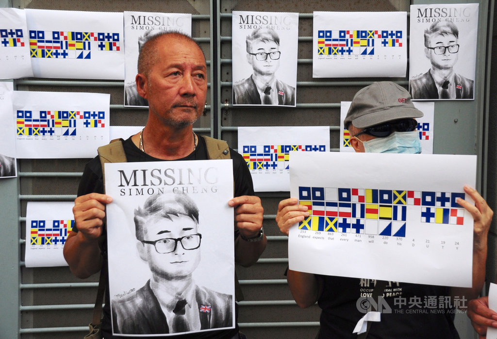 數10位港人21日聚集在英國駐港總領事館外,高喊「Save Simon now, Delay no more 」口號,並將印有鄭文傑頭像的海報張貼在領事館外牆,呼籲英國政府積極救援。中央社記者沈朋達香港攝 108年8月21日