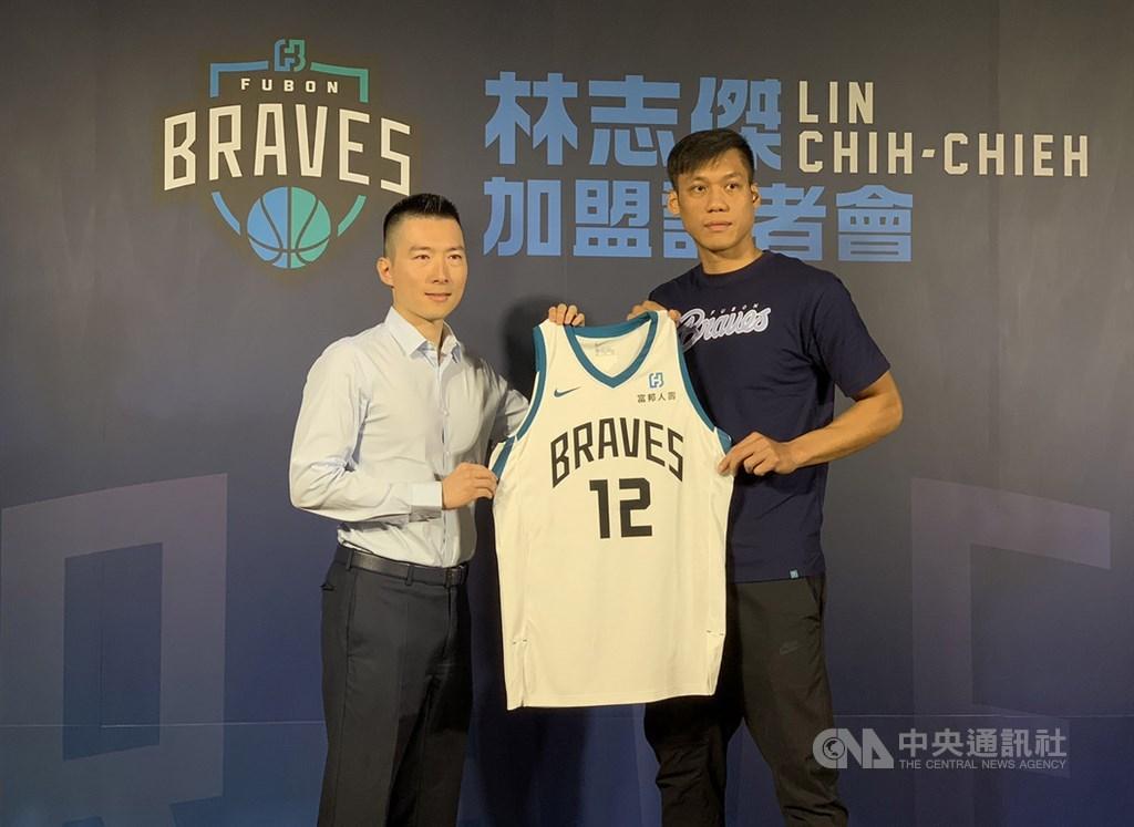 台灣籃球好手「野獸」林志傑(右)加盟富邦勇士記者會22日下午在台北舉行,富邦育樂總經理暨富邦勇士隊領隊蔡承儒(左)送上球衣。中央社記者張新偉攝 108年8月22日