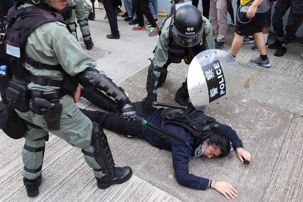 香港「反送中」示威者24日在九龍觀塘舉行遊行。結束後,抗議人士轉進包圍附近的牛頭角警署;警方在4時30分左右舉紅旗,警告示威者不要衝擊,並於隨後施放催淚彈並動手抓人。中央社記者張謙香港攝 108年8月24日