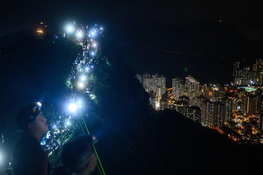 香港23日晚間出現「香港之路」活動,效法30年前波羅的海抗爭,盼各界關注「反送中」訴求。圖為民眾自發登上獅子山山頂,以手機燈光照亮山脊線。(法新社提供)