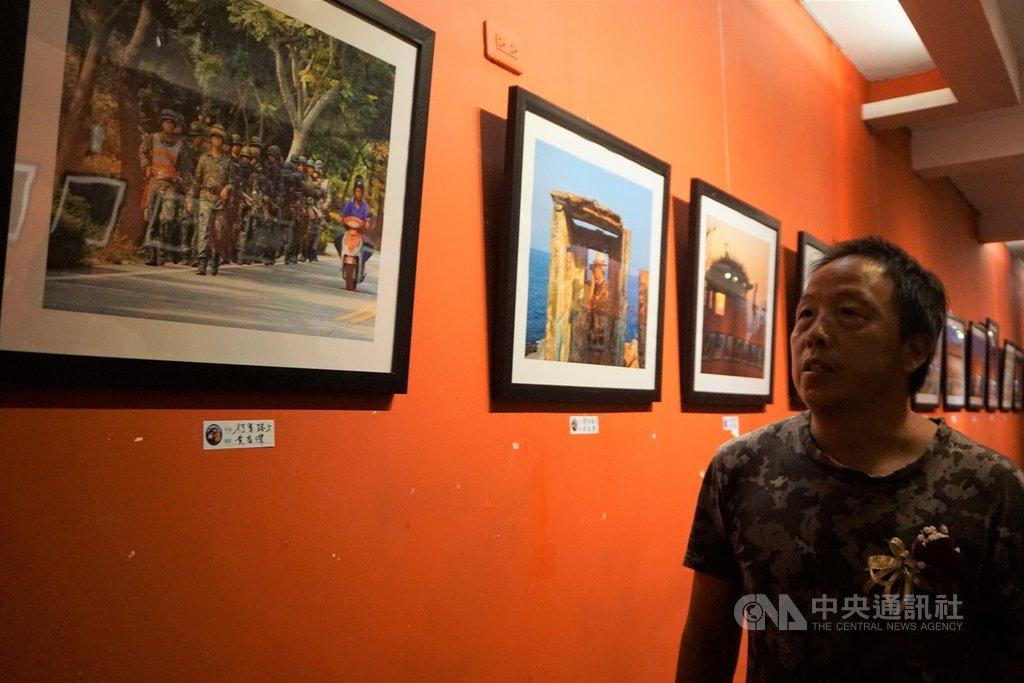 「戰地.讚地」攝影聯展正在金門縣文化局展出,金門縣攝影學會成員黃家傑的「行軍路上」,勾起觀者回憶,學會理事長許進西(圖)等人感嘆,現在街上都很難看到軍人了。中央社記者黃慧敏攝  108年8月25日