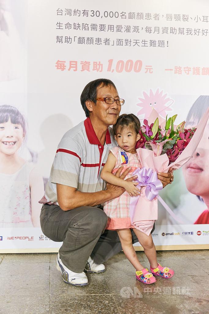 羅慧夫顱顏基金會25日舉行記者會,為顱顏患者發聲。患有巨口症的小華(右)因家庭缺乏就醫資訊,直到2歲才接受治療,外公(左)是她唯一的依靠。(羅慧夫顱顏基金會提供)中央社記者陳偉婷傳真  108年8月25日