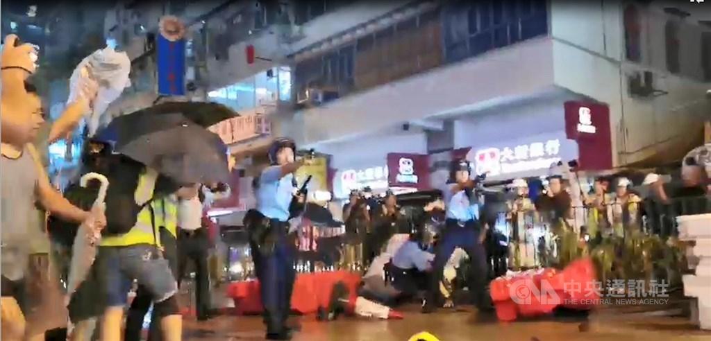 香港「反送中」遊行今晚疑似首度出現警方發射實彈。入夜後,有約10名員警在抗爭現場遭示威者包圍追打,被圍員警拔出隨身的左輪手槍對空鳴槍示警,示威者一哄而散,並遭增援的員警追捕。中央社記者張謙香港攝 108年8月25日