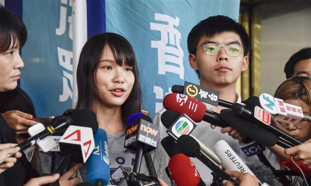 香港眾志祕書長黃之鋒(右)和成員周庭30日上午被捕,下午在東區裁判法院出庭,裁判官同意兩人各以港幣一萬元現金交保外出,但要遵守宵禁令等。(共同社提供)