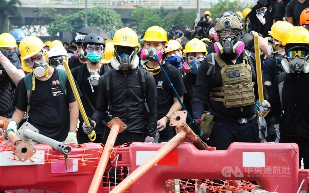 美國總統川普30日表示,因為美中貿易談判,讓中國緩和對香港示威活動的反應。圖為反送中24日觀塘遊行,有示威者包圍牛頭角警署,並在路障後全副武裝與警對峙。(中央社檔案照片)