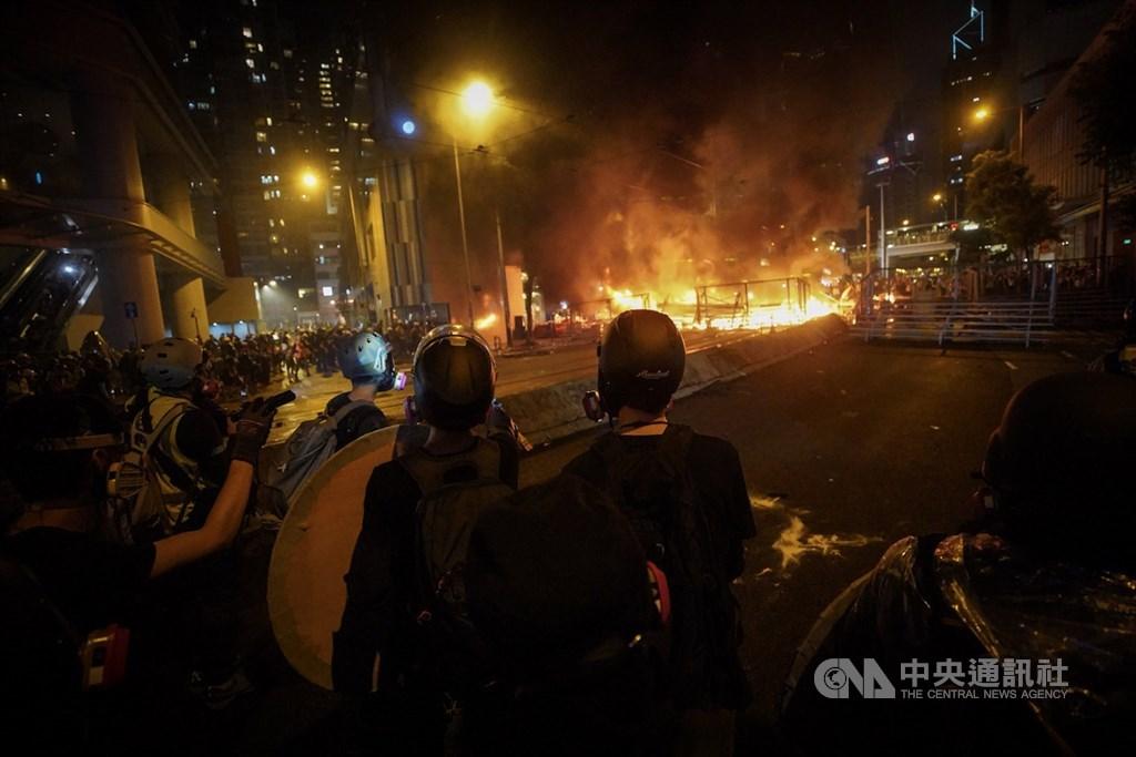 香港反送中運動31日傍晚上演暴力抗爭場面,除警方發射催淚彈、出動水砲車外,示威者也頻丟汽油彈等,雙方對峙至入夜仍持續,灣仔一帶街道燃起熊熊火光。中央社記者吳家昇香港攝 108年8月31日