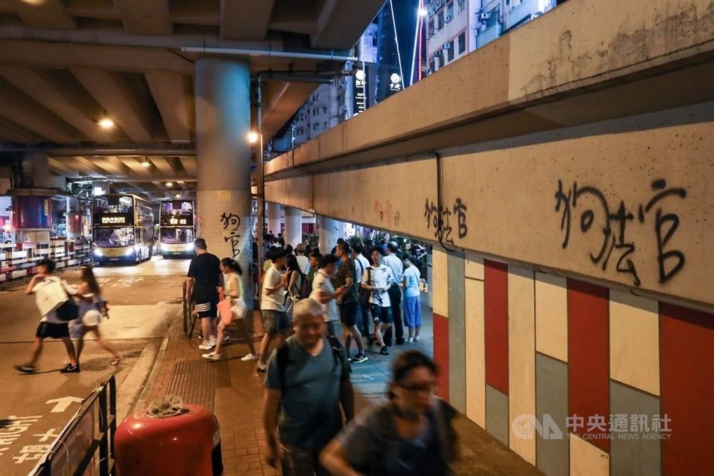 日常的香港街頭一切如常,只有牆上的噴漆提醒著現在仍在抗爭中。