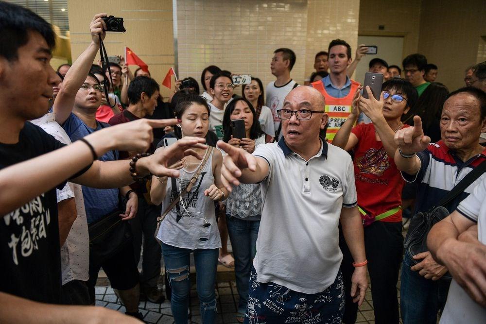 香港14日多地出現零星的反制「反送中」活動,其中一批手持中國國旗的人士,在九龍灣淘大商場聚集並唱中國國歌「義勇軍進行曲」,又高叫支持警察,與「反送中」支持者頻傳衝突。(法新社提供)